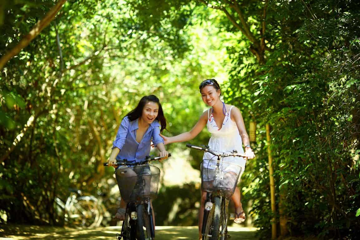 Two girls bike riding in the forest.