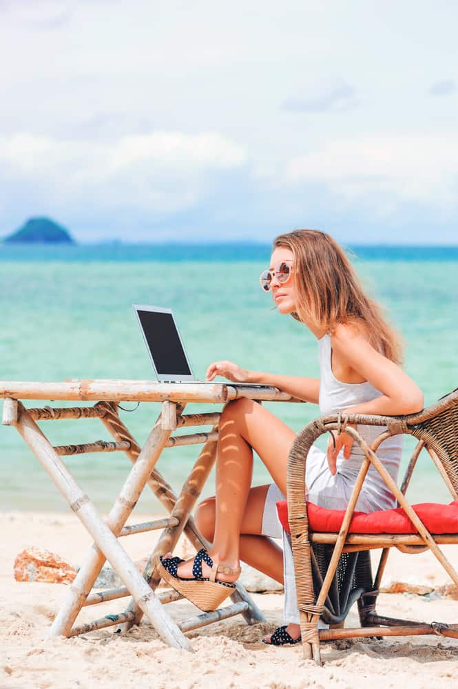 Girl Freelancer working on the beach scaling her freelance business