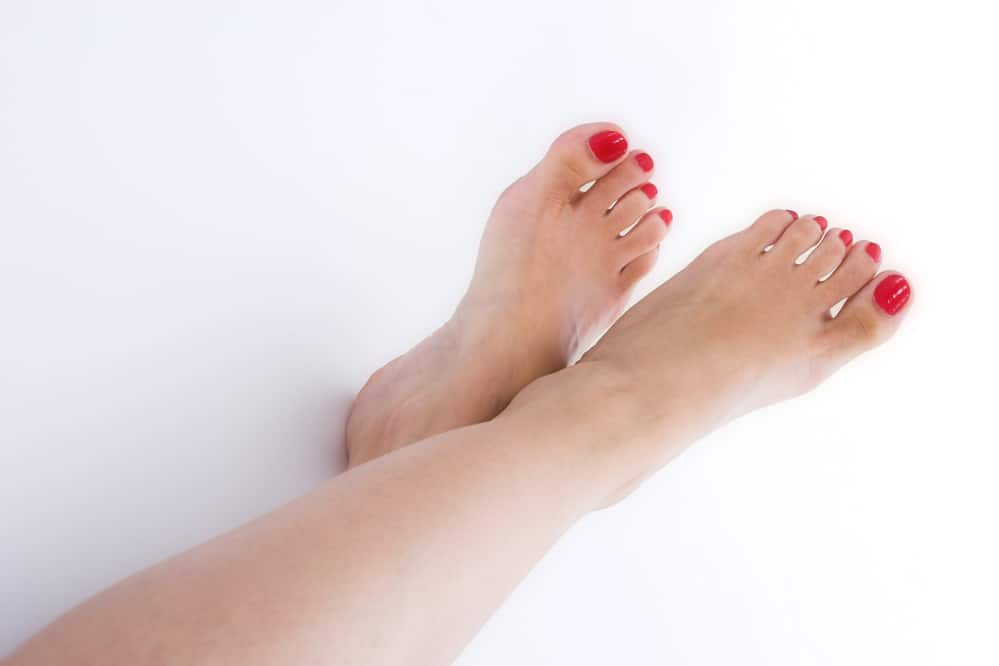 Learn to pose in different positions to sell feet pics. Photo showing crossed over bare feet with red nail polish on.
