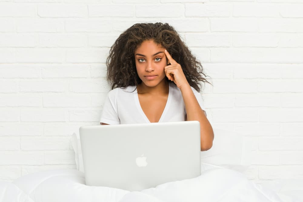 Young african american woman sitting on the bed with laptop focused on working through the Comprehensive Copywriting academy course and becoming a successful copywriter