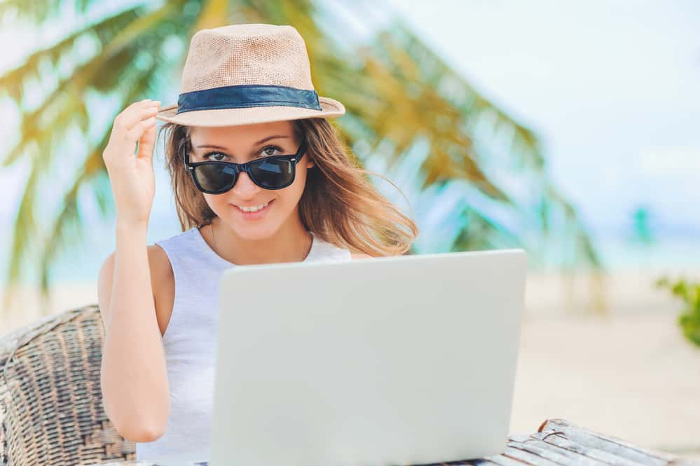 Young attractive woman in sunglasses and dress with hat working in laptop on the beach. Girl Freelancer working - our recommended money saving, blog and money making resources