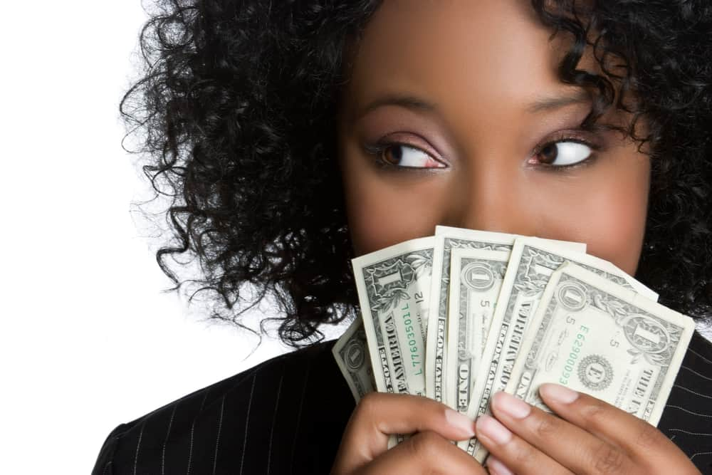 Save money resources from Budgeting is a Challenge. Woman holding dollar notes.
