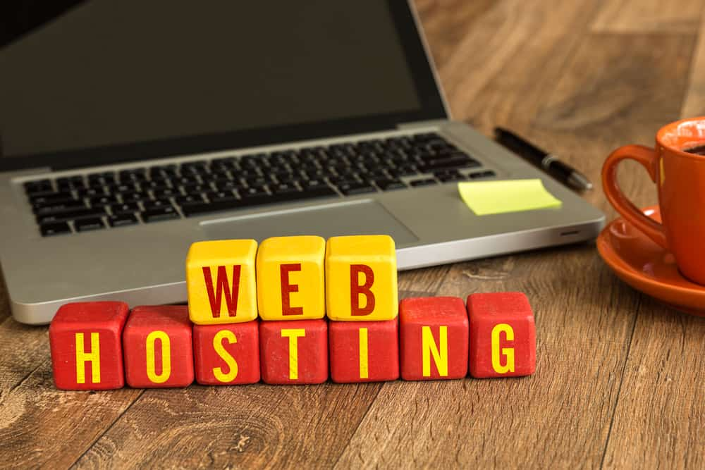 Laptop on desk with letters Web Hosting in front of it. We discuss why we think Bigscoots is the best managed WordPress hosting